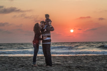 a mother and father lifting up their son on a beach at sunset