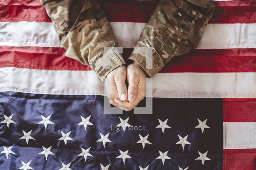 military man with praying hands over an American flag