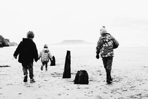 children in winter coats running in sand on a beach