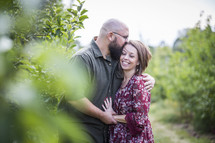 a couple hugging in an apple orchard