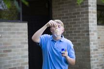 teen boy blowing bubbles