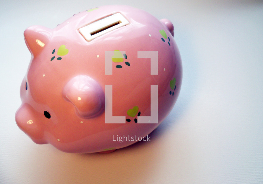 The Top side view of a pink piggy bank decorated with blue and green flowers against a solid white background enticing children to save money for college, buying a house or saving for the future.