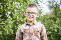 smiling boy standing in an apple orchard