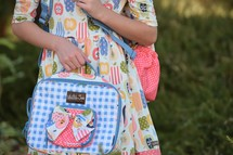 a student holding a lunch box and book bag
