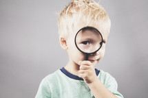 child looking through a magnifying glass