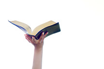hand holding an open Bible in the air