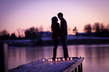 silhouette of a couple on a dock and candles