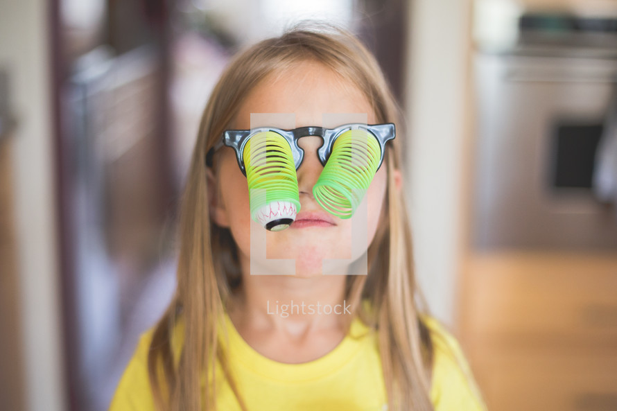 Young girl wearing toy glasses with dangling google eyes.