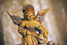 Figurine of an angel seated on the rocks playing a drum; a Christmas decoration.