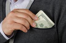 Hand putting folded hundred dollar bills in a pocket.