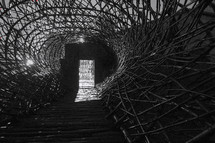 woven sticks to form a tunnel and hole near the door