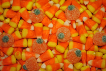 Candy corn and gumdrop pumpkins for Halloween or Thanksgiving; closeup, texture.