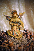 Figurine of an angel seated on the rocks playing a drum; a Christmas decoration set among pine cones and Spanish moss.