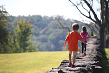 children walking on the top of a stone wall outdoors