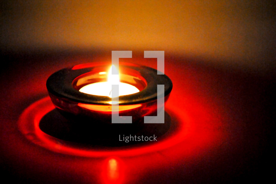 One single votive light in a red glass holder.