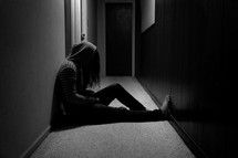 teen girl with her head held down sitting in a hallway