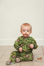 Toddler boy sitting on the floor eating a cookie, with a chocolate mess on his face.