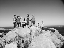 friends gathered at the top of a moutain enjoying the views