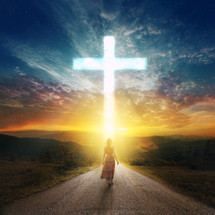 woman walking down a road towards a cross in the sky
