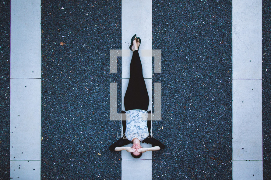woman lying on a white line