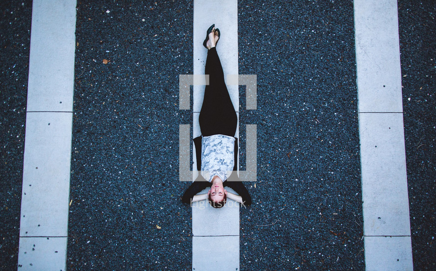 A woman lying on white lines in a parking lot.