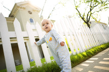 Little boy leaning on white picket fence