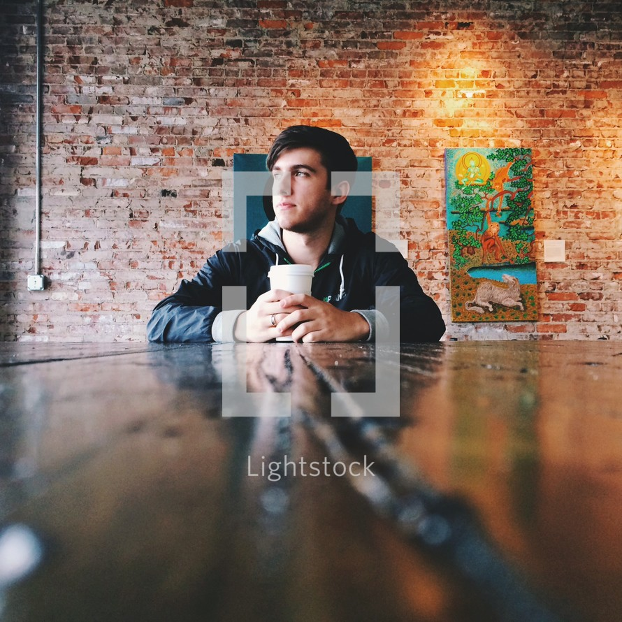 A man sitting in a cafe drinking coffee