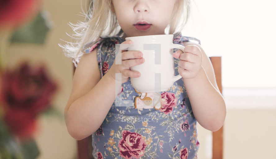 a toddler girl holding a mug