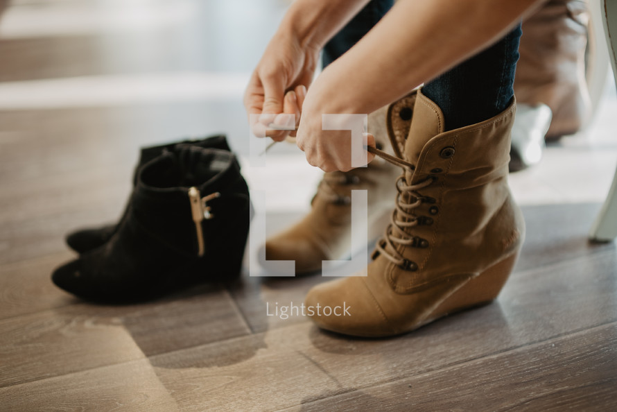 a woman putting on boots