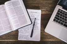 open Bible and notes on a notepad and pen and laptop