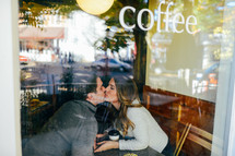 A couple kiss in the window of a coffee shop.