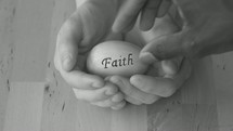 cupped hands holding an egg with the faith hope on it