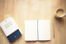 Spanish Bible, journal, and coffee mug on a wood table