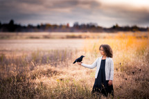 a child in a field holding a crow in her hand