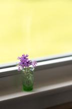 purple flowers in a glass in a window sill