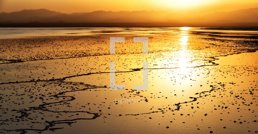 sunset over a salt lake shore
