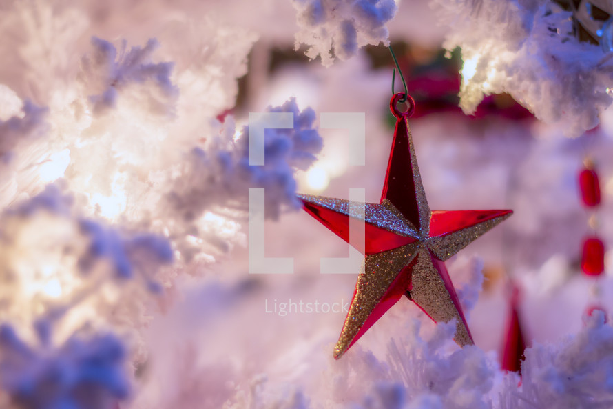 red star Christmas ornament on a white Christmas tree
