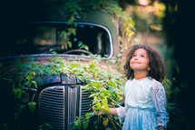 a little girl standing in front of a vintage car covering in ivy