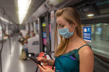 young woman wearing a face mask on a subway train
