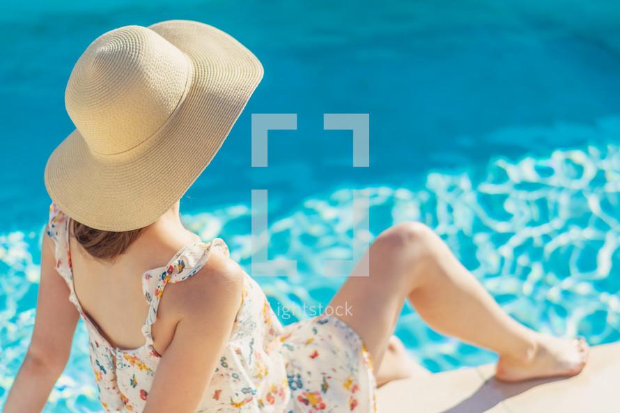 a woman sitting beside a pool
