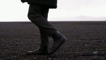 a man walking across a flat landscape