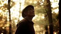 elderly man looking up to God in a forest