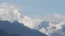 clouds moving over snow covered mountain peaks