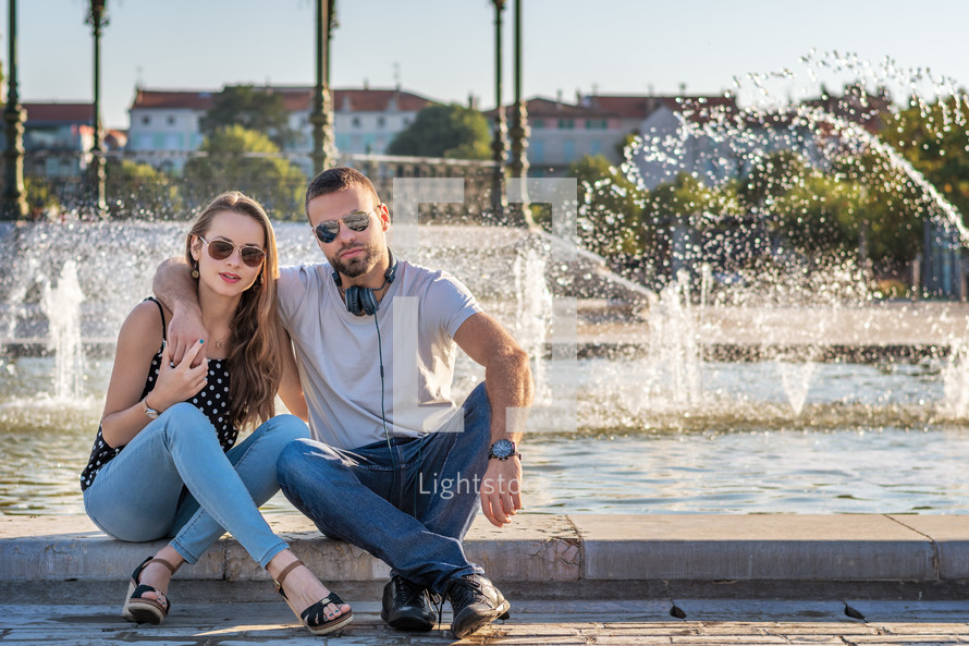 a couple in the city in front of a fountain