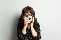 a woman holding a vintage camera