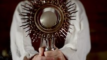 Priest holding a monstrance and blessing a Bible with the sign of the cross.