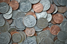 A heap of assorted US coins of many denominations. closeup