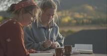 Teen girls reading Bible outdoors at a fall retreat