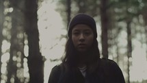 a sad teen girl standing alone in a forest