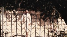 Jesus walking in a  modern garden